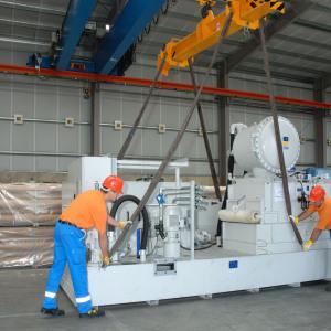 Zum Maschinentransport arbeitet hier ein Mitarbeiter, der in orange/blauer Kleidung sich um die Aufhängung kümmert. Darunter steht eine graue, unverpackte Maschine.
