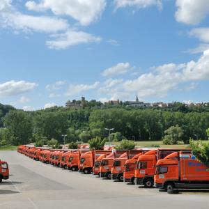 Man sieht eine in die Tiefe reichende Reihe geparkter Jumbo-Lastzüge in orange. Vorne links ist gepflasterter Hof, im Hintergrund Bäume und Wiese, der Himmel ist blau mit weißen Wolken.