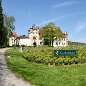 """Man sieht die Burg Jagsthausen in einem park-ähnlichen Gelände davor. Hier steht auch eine große grüne Tafel mit der Aufschrift """"Götzenburg""""."""