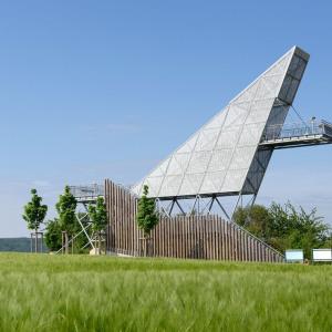 Man sieht den hochmodernen Aussichtsturm, der in der Form eines steilen Dreiecks futuristisch anmutet. Davor stehen Bäume und ein Zier-Zaun.