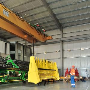 Oben sieht man einen gelben 32-Tonnen-Kran in einer Lagerhalle. Darunter ist ein Mitarbeiter vor zwei großen Maschinen, eine grüne und eine gelbe.