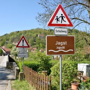 """Man sieht auf eine Brücke über die Jagst und bildfüllend auf das braune Hinweisschild """"Jagst"""" und mit kleineren Buchstaben darunter """"Jogscht"""" steht dort zu lesen."""