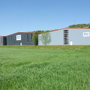 """Man sieht drei Lagerhallen in 3 Grautönen und jeweils mit einem Schild """"Rüdinger Spedition"""" darauf. Davor blickt man auf ein grünes Feld."""