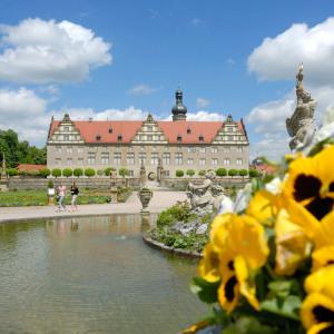 Eine Schokoladenansicht von Schloss Weikersheim bei bestem Wetter, blauem Himmel und weißen Wolken. Das Schloss liegt malerisch in der Sonne. Im Vordergrund ist ein Wasserbecken und ganz rechts sind gelbe Stiefmütterchen mit schwarzen Sprenkeln..