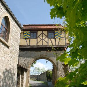 Ein verspieltes malerisches Innengebäude in der Burg Krautheim besteht aus viel Fachwerk. Unten ist ein großer Torbogen, rechts ist ein Baum.