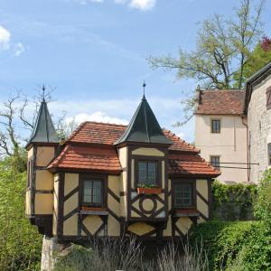 Ein besonders schönes Gebäude innerhalb der Burg Krautheim. Das Haus ist gelb, das Fachwerk dunkel. Rechts ist hellgrünes Laub. Der Himmel ist blau.