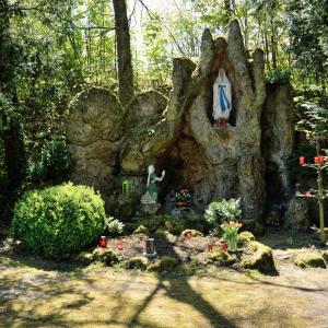 Man sieht eine Felsgrotte mit einigen christlichen Figuren. Rundherum ist sommergrüne Natur.